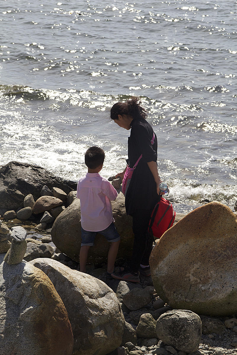 Inukshuk, mother and son trying, Vancouver