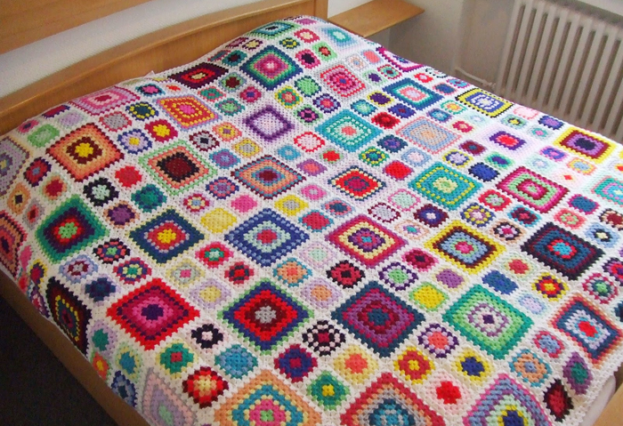 Crocheted granny blanket with different sized squares