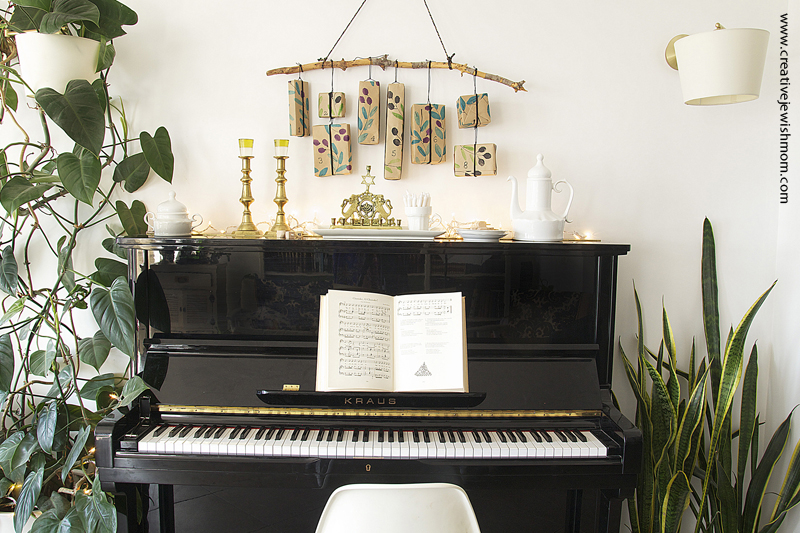 Hanukkah Potato Print Gifts On A Branch Over Piano With Plants over black piano