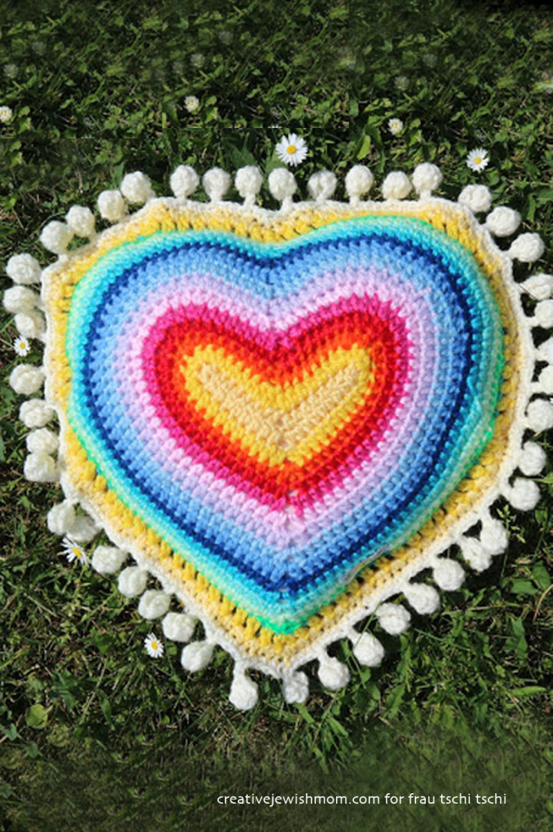 Crocheted heart pillow with pom pom trim