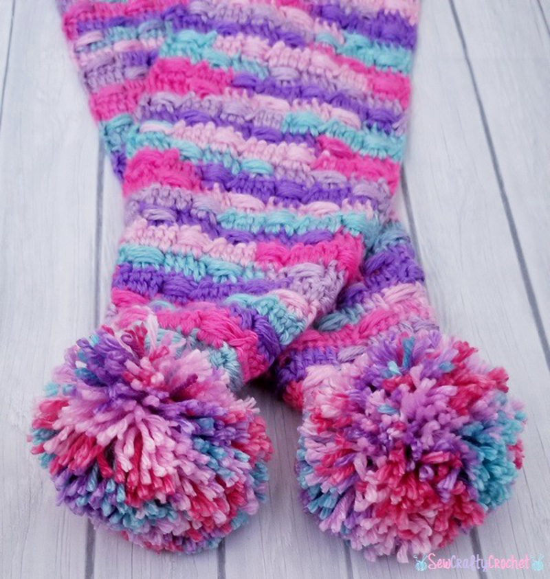 Crocheted-unicorn-colors-scarf-with-pom-poms