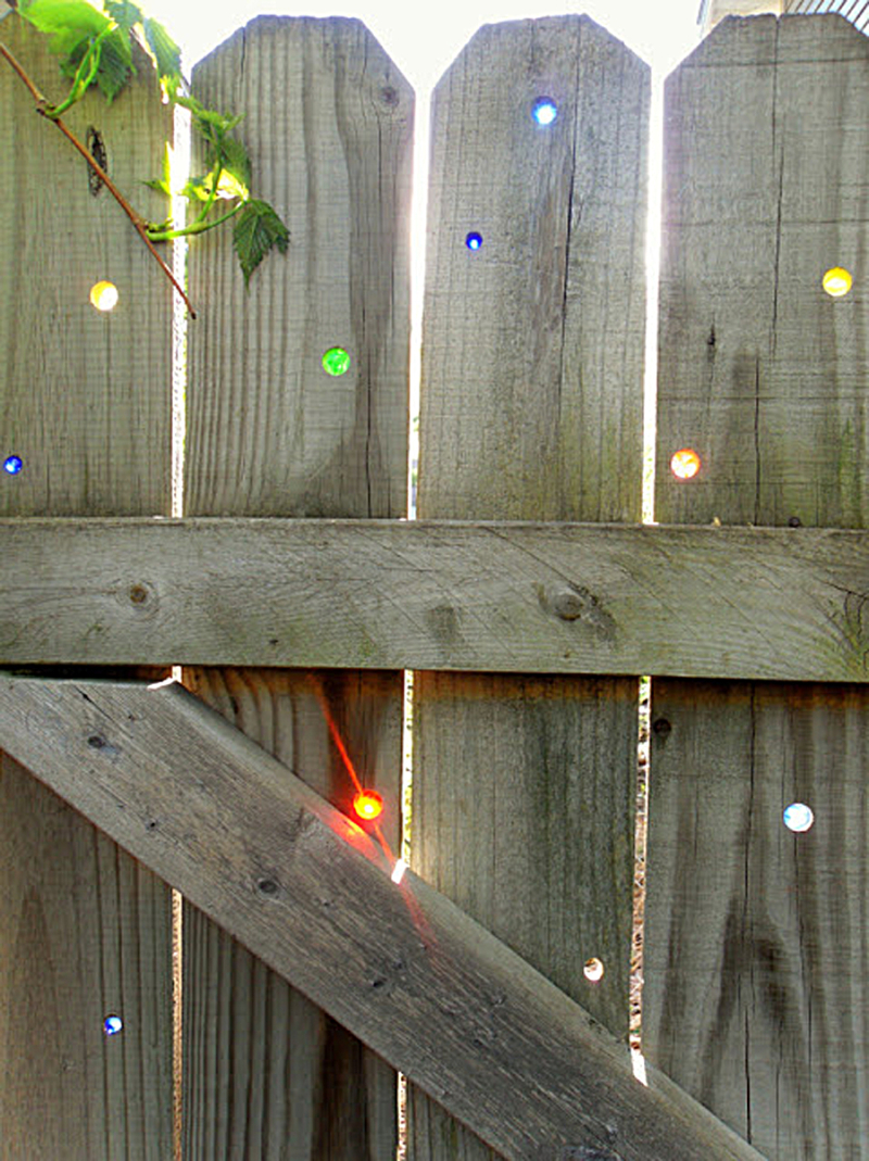 Marbles-inlaid-in-wood-fence