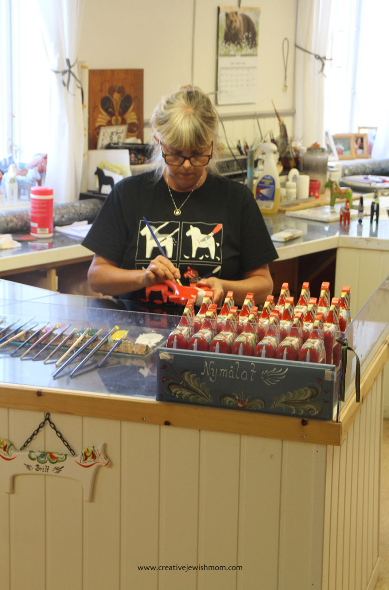 Sweden-woman-painting-wooden-horse