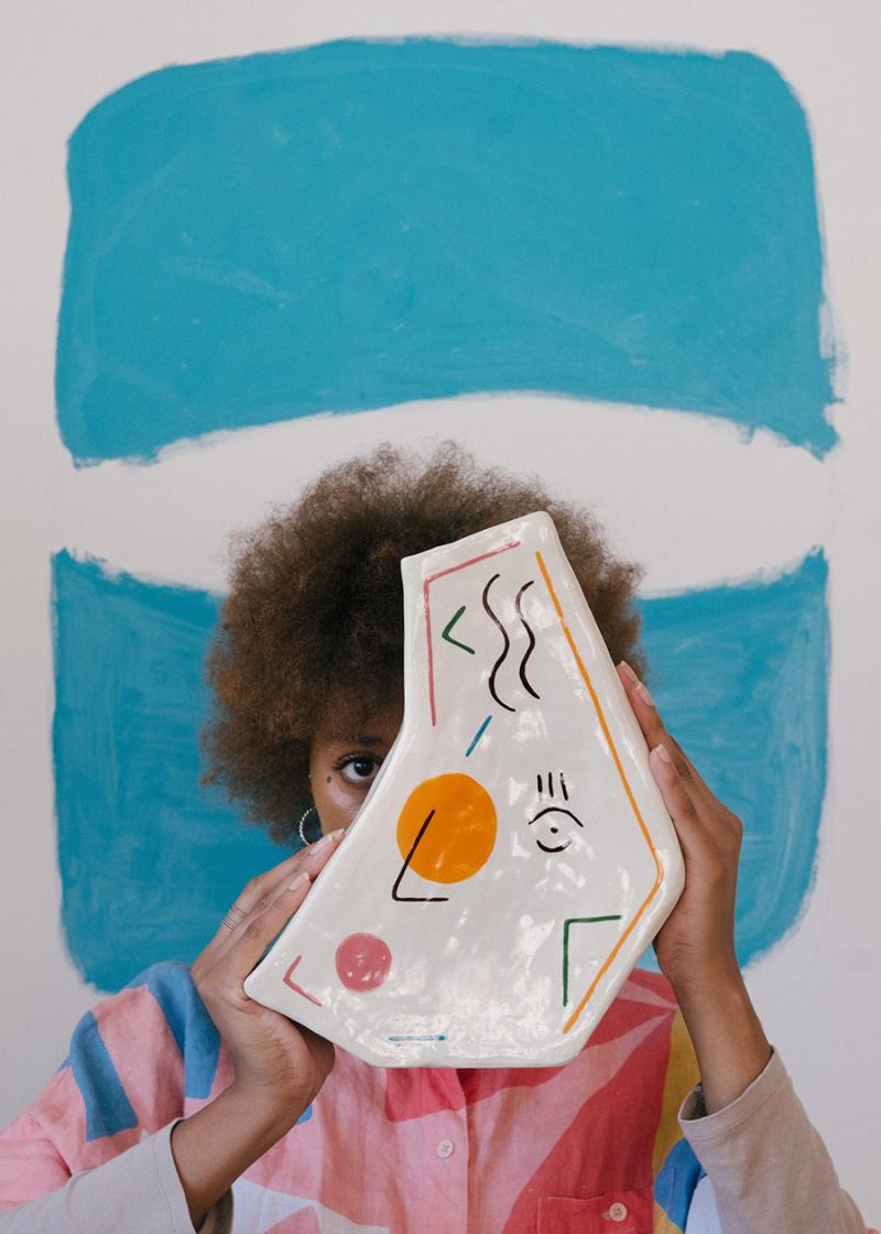 Creative-female-artist-with-painted-vase-in-modern-studio-3817583