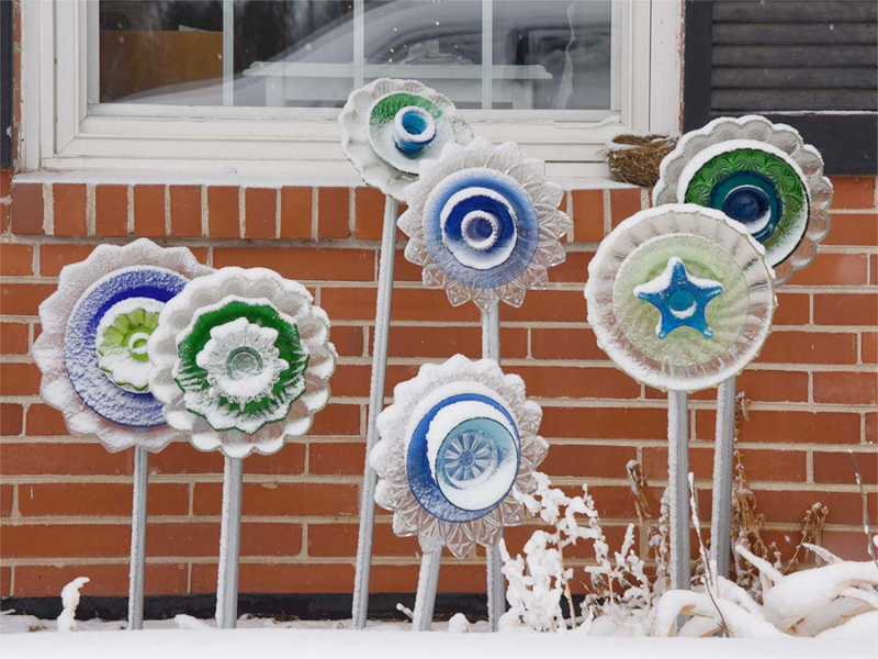 Glass flower yard ornaments in snow